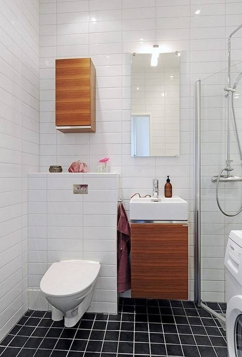 This small bathroom is simple in style and decoration but the artful light  fixtures and medicine chest bring the eye to the ceiling, visually  enlarging the